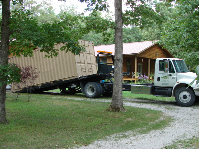 A Best Value truck delivering a storage container to a residence